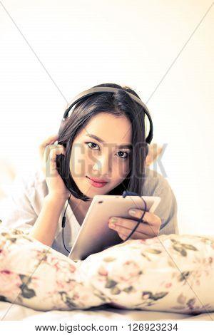 Girl Listen Using Headphone And Mobile Phone.