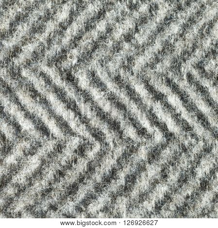 Wool fleecy fabric with geometric black and white pattern texture. Close up fragment of the top view.