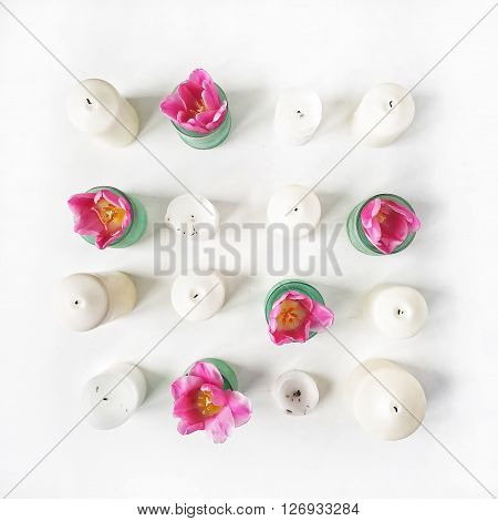 Overhead view of white candles and pink tulips in vases isolated on white background