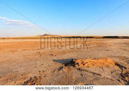 The desert landscape of the salt plains. Lone hill. A hot summer evening and the blue sky