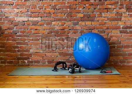 The Mat, Fitball, Rope, Dumbbells And Stand Push-ups Lie On The Floor In The Gym