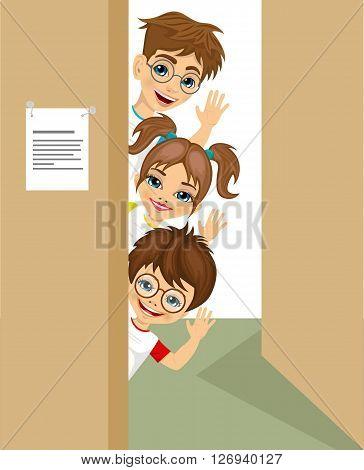 portrait of cute children peeking of the door waving. Preschool concept.