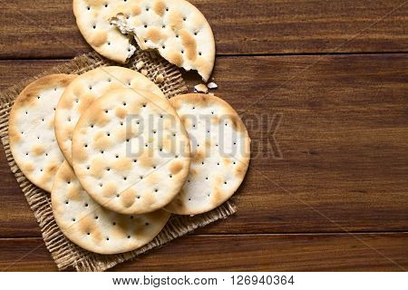 Saltine or soda crackers photographed overhead on dark wood with natural ight