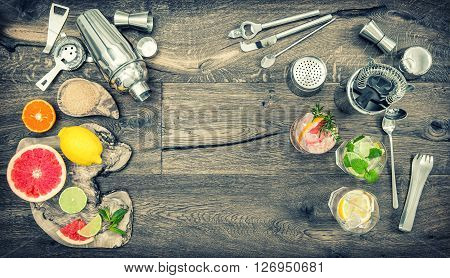 Fruit drinks with ice. Cocktail making bar tools shaker glasses. Flat lay. Vintage style toned picture