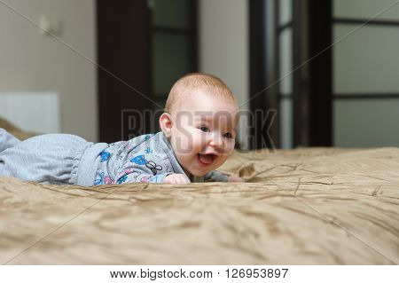 Baby girl lying on belly on bed in bedroom with golden linens. Charming 5-month-old girl smiling and grimacing. Home interior in background.
