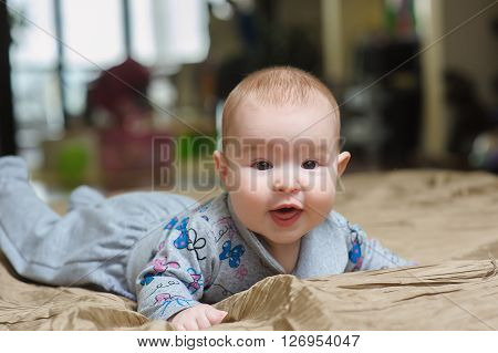 Baby girl lying on belly on bed in bedroom with golden linens. Charming 5-month-old girl smiling and grimacing, with interest looking at the camera. Home interior in background.