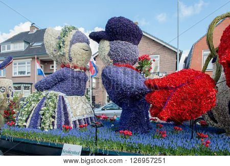 HILLEGOM, THE NETHERLANDS - APRIL 23, 2016: Moving platform with a huge frame made in a form of a traditional Dutch kissing couple. Taking part in the  traditional flowers parade