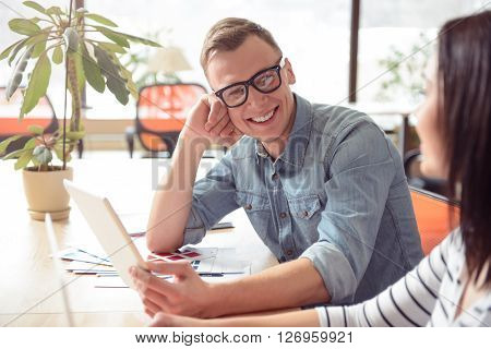 Pleasant interlocutor. Cheerful delighted smiling man sitting at the table   and using tablet while talking with his colleague