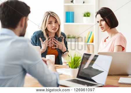 Young man is explaining to colleagues his ideas and showing a document. The blond woman is looking at it with disagreement and pity. Another lady is listening to men attentively