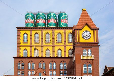 Qingdao China 20/04/2016 Main building of the Qingdao brewery with four cans of beer on the rooftop and a clock tower