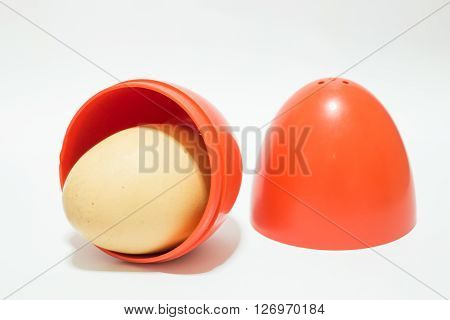 Red plastic egg on white table stock photo