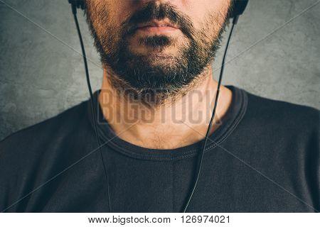 Unshaven adult man listening to music on headphones enjoy favourite song half face low key portrait