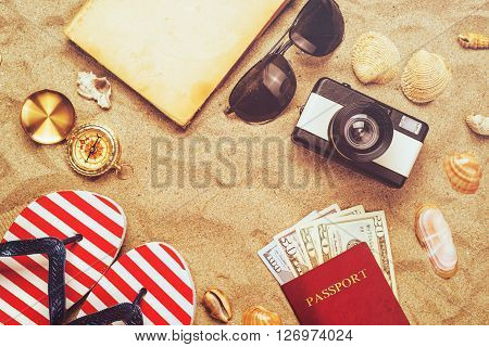 Summer vacation accessories on tropical sandy ocean beach holidays abroad - summertime lifestyle objects and US American dollars in flat lay top view arrangement in warm sand.
