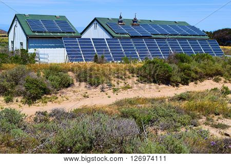 Modern solar panels taken on the roof and beside a home taken in the rural countryside