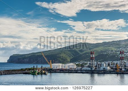 Le Port Reunion island France - December 24 2015: Industrial facilities in the Le Port on Reunion island France. It is the main harbour city of the island as with any Island they are dependent on imports for survival.