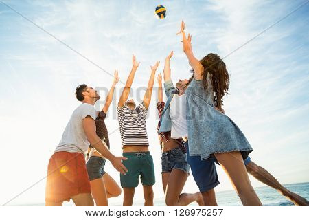 Friends trying to catch volley ball on a sunny day