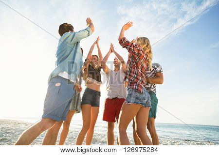 Friends doing high five on the beach on a sunny day