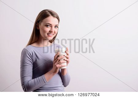 Get the energy boost. Cheerful beautiful positive woman smiling and drinking coffee while standing isolated on grey background