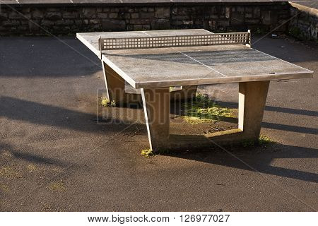 robust outdoor ping pong table from concrete with a network of metal on an asphalt area copy space