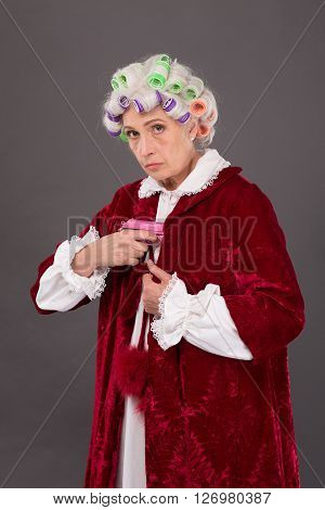 Strict and demanding elderly lady with rollers on hiding pink plastic gun under blouse in studio. Studio shot. Serious glance.