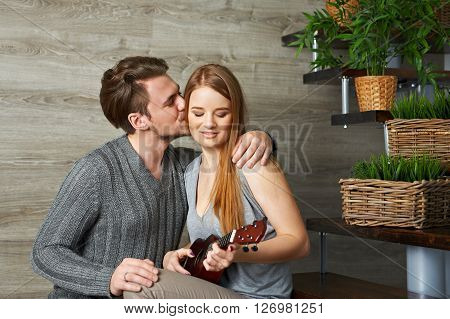 Young girlfriend playing ukulele for her boyfriend on stairs. Boyfriend kissing her.