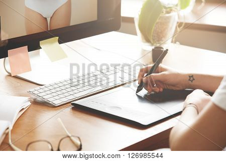 Close-up of woman's hands retouching photos using digital tablet. Cropped portrait of young female freelancer using graphic tablet and computer while working at home. Selective focus film effect