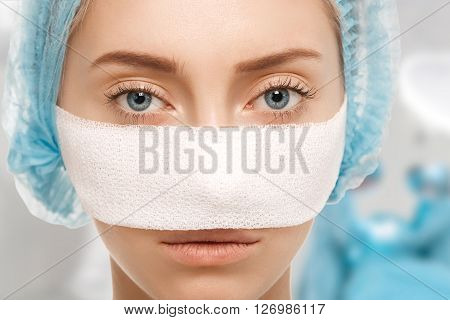 Close-up Portrait Of Young Caucasian Woman With Nose Bandages After Cosmetic Surgery Looking At The