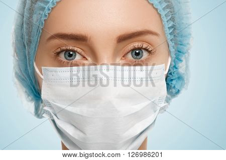Close Up Isolated Portrait Of Young Caucasian Female Surgeon Wearing Surgical Mask And Blue Cap Look