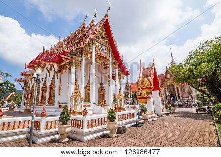 Red and gold thai buddism church with blue cloudy sky