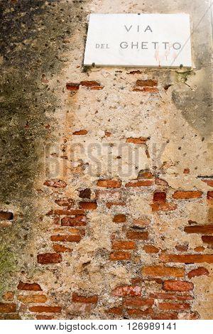 Road Sign on a brick wall reading: via del ghetto