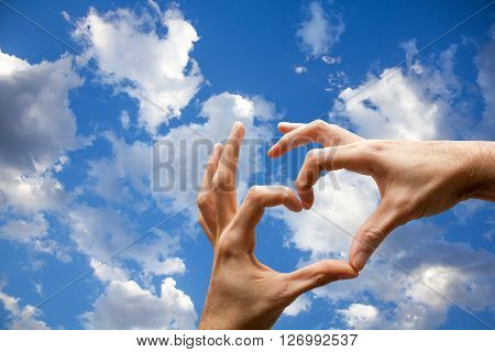 Hands with heart shape on the blue sky with clouds.