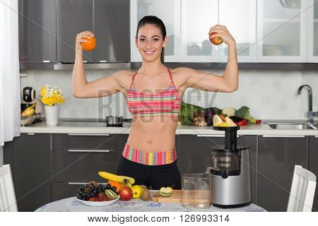 young fit woman in the kitchen front double biceps with an orange and an apple