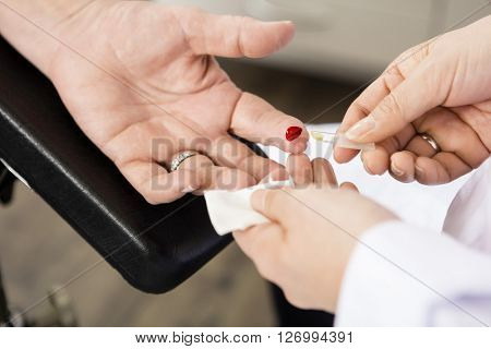 Doctor Taking Blood Sample Of Patient In Clinic