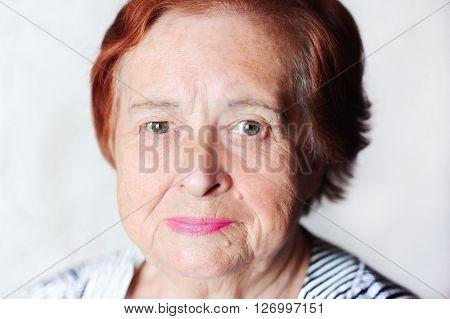 Elderly woman smiling indoors. Looking at camera. Senior female.