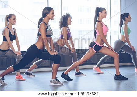 Great stretching. Side view of beautiful cheerful young women with perfect bodies in sportswear doing stretching with smile while standing in front of window at gym