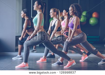 Stretching with smile. Side view of beautiful young women with perfect bodies in sportswear exercising with smile at gym