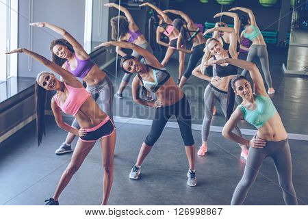 Aerobics with girls. Young beautiful cheerful women with perfect bodies in sportswear exercising and looking at camera with smile at gym