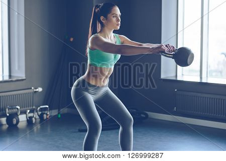 Perfect cross training. Side view of young beautiful woman with perfect body in sportswear working out with kettle bell at gym