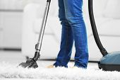 Woman cleaning the carpet with vacuum cleaner in the living room poster