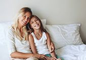 Mom with her tween daughter relaxing in bed, positive feelings, good relations. poster