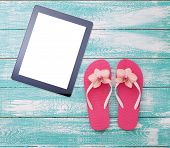 Blank empty tablet computer on beach. Trendy summer accessories on wooden background pool. Flip-flops on beach. Tropical flower orchid. Flat mock up for design. Top view. square poster