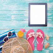 Blank empty tablet computer on beach. Trendy summer accessories on wooden background pool. Sunglasses, orange juice and flip-flops on beach. Tropical flower orchid. Flat mock up for design. Top view. poster