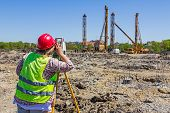 Woman surveying is measuring level on construction site. Surveyors ensure precise measurements before undertaking large construction projects. poster