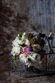 Bouquet from pink tulips violet grape hyacinths white anemones violet veronica and white buttercup with violet ribbon lying in the metal basket with glass bottle on rought metal background with rust poster