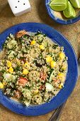Quinoa salad with sweet corn olive tomato cucumber and chives on plate photographed overhead on slate with natural light poster