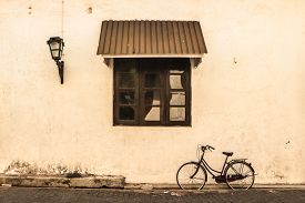Picture depict a bicycle parked beside a wall by a  person who has come to work. This picture was taken in Galle, Sri Lanka.