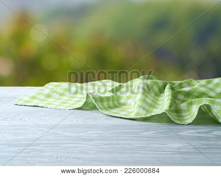 Empty Wooden Table With Green Checked Tablecloth Over Nature Bokeh Background