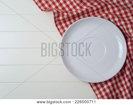 White Plate On Red Checked Tablecloth On Table Background. Top View