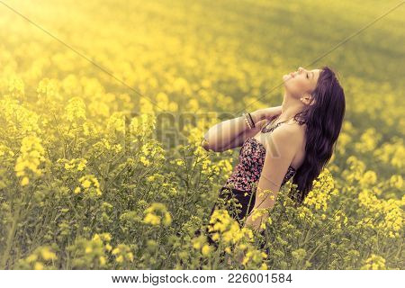 Beautiful Woman In Meadow Of Yellow Flowers With Head Up. Attractive Genuine Young Girl Enjoying The