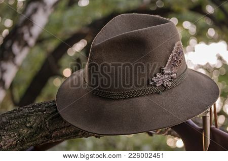 Green Hunting Hat With Hunting Accsesorieson The Background.